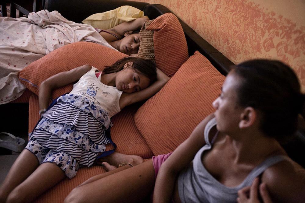 Villaggio Coppola, Castel Volturno, Campania. Claudia e' sul divano che dorme accanto alle sue due figlie Federica e Alessandra.