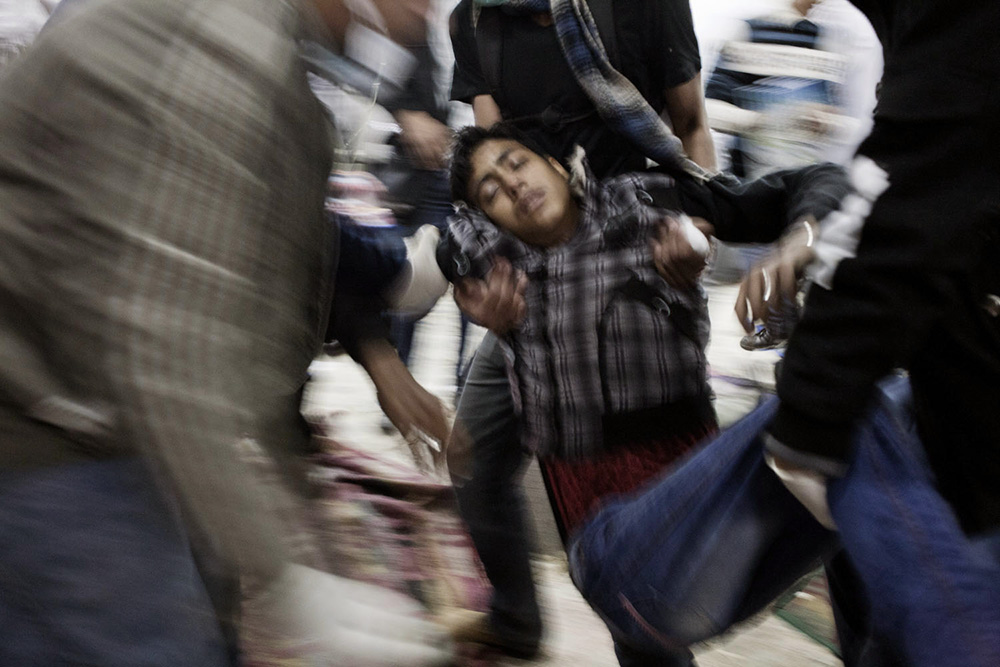 Cairo, Egitto. Un ragazzo svenuto viene soccorso dopo aver inalato gas lacrimogeno durante gli scontri in Piazza Tahrir.