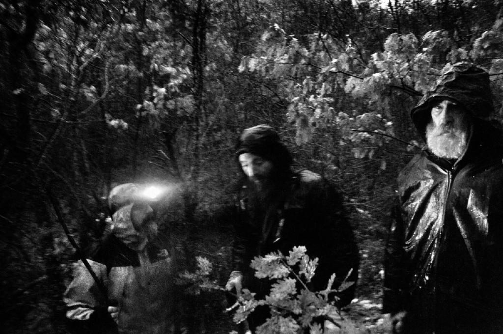 """Da """"Forgotten Memories"""". Il """"badnjak"""" - il ceppo di Natale dei cristiano-ortodossi serbi. Il rito consiste nel bruciare un ceppo di quercia fuori dai portali della chiesa poche ora prima della mezzanotte durante la Vigilia di Natale. Nei giorni che precedono le celebrazioni natalizie, i monaci salgono sulle montagne (scortati dai militari) per cercare il ceppo da tagliare. Dečani, Kosovo."""