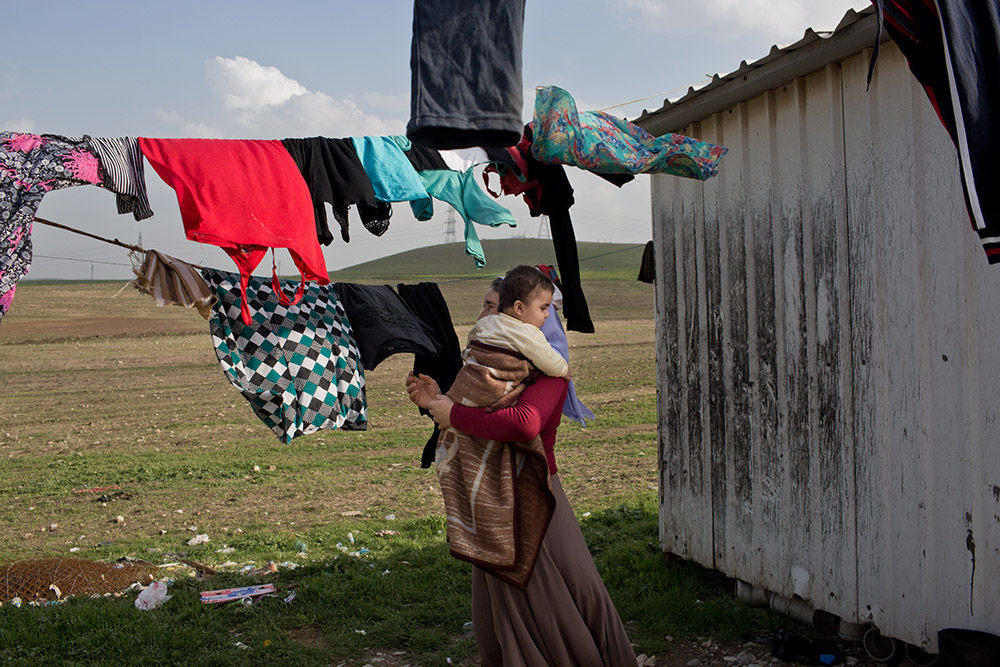 17/02/15 -Tanjero, Iraq: Ghazal hangs up the family laundry while holding her grandson, Mazal. The family of Yezidis, displaced from Sinjar, live next to an oil refinery in the Kurdish Region of Iraq. The young men run the refinery 24 hours a day with little to no safety equipment. © Sebastian Meyer/Metrography