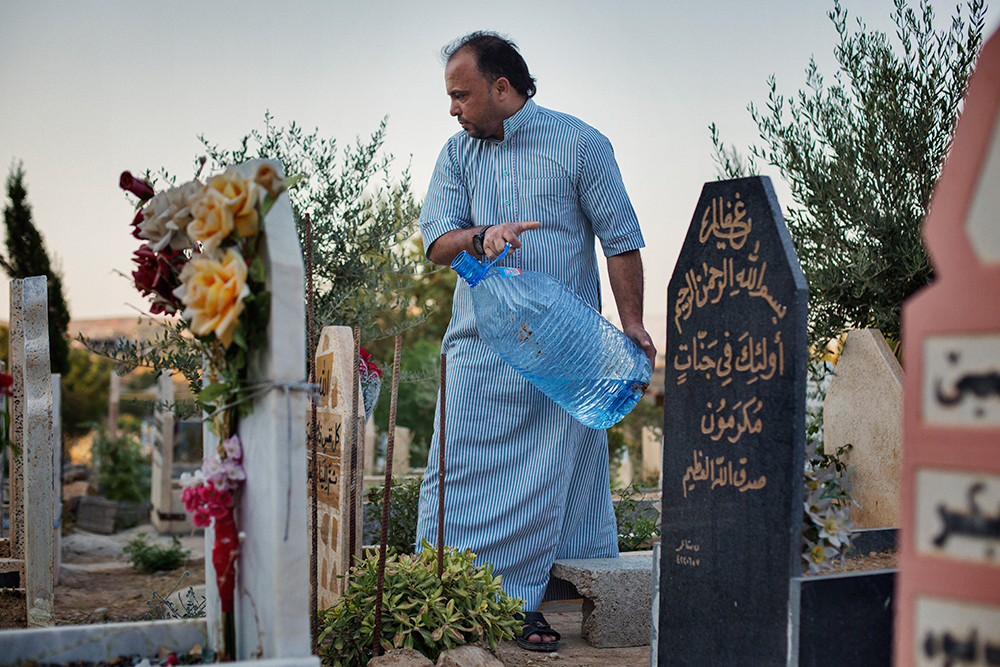 28/08/15. Shaqlawa, Iraq. - Jaser, from Falluja, washes his father's grave in the new part of Shaqlawa's graveyard. His father died two months after arriving to Shaqlawa as a displaced person, early 2014. © Dario Bosio/Metrography