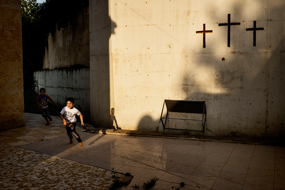 20/05/15. Shaqlawa, Iraq. - A displaced Christian boy from Qaraqosh inside the courtyard at Al Shuhada church. Around 800 Christian families have arrived to Shaqlawa since August 2014. Most of them have now been moved to shipping containers in a new camp in Erbil. © Stefano Carini/Metrography