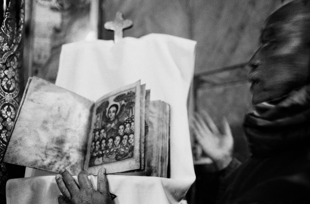 Gerusalemme. Il custode di una chiesa etiope mostra un'antica copia della Bibbia. La comunità cristiana comprende Cattolici, Ortodossi, Copti egiziani ed etiopi. Dicembre 2012. © Linda Dorigo