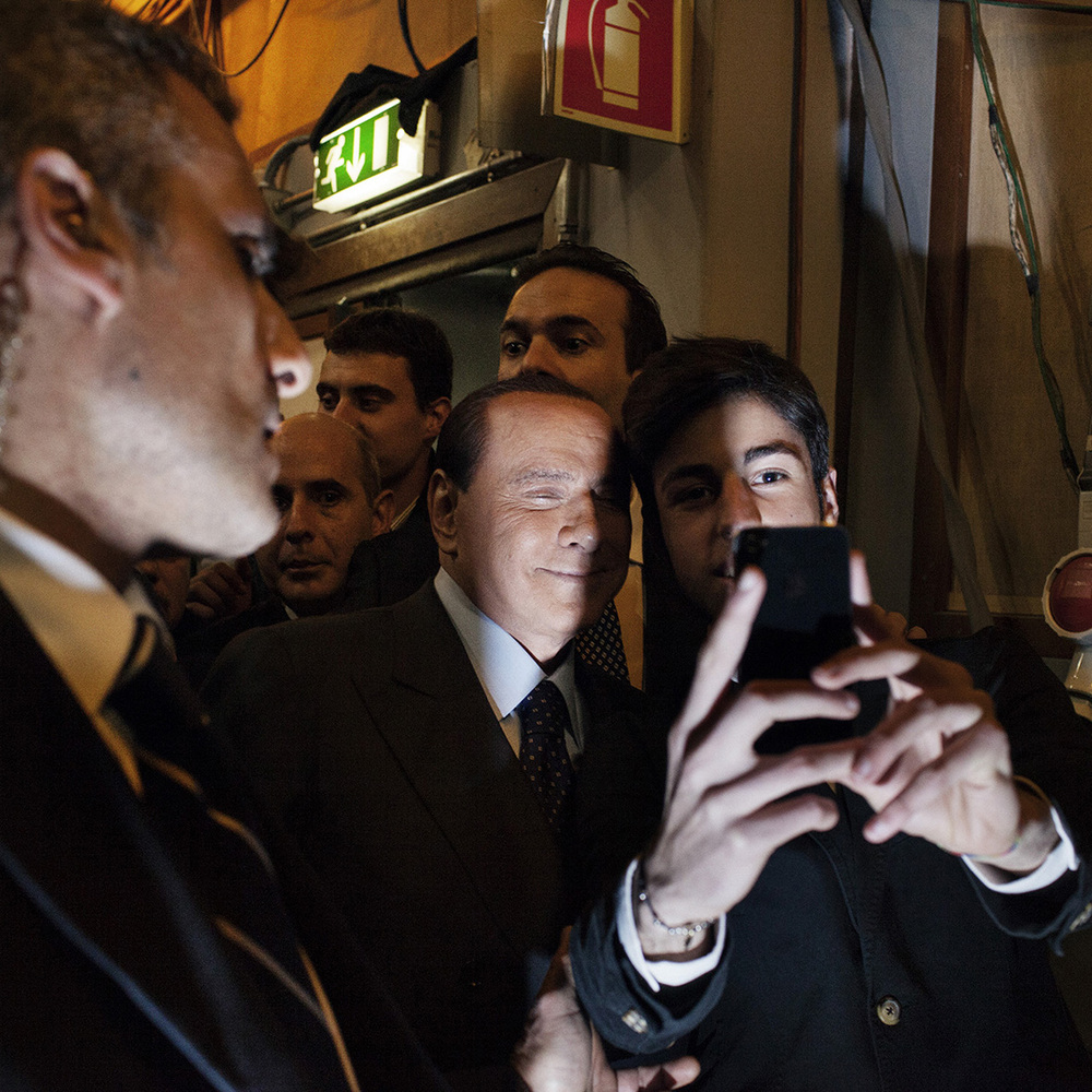 Rome, February 2013. Silvio Berlusconi is being photographed by a fan while he exits the studios of tv talk show