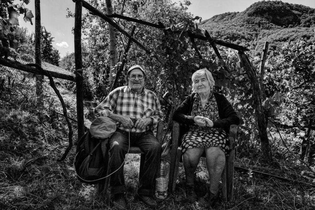 """""""Gli Spaesati"""", I coniugi Alberto e Nazzarena Gigli, originari di Trisungo, seduti nel loro orto ad Arquata del Tronto. © Giovanni Marrozzini"""