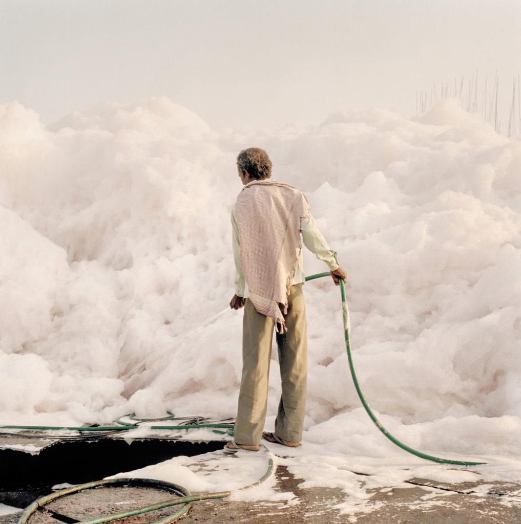 Un operaio cerca di eliminare un accumulo di schiuma causato dalle scorie industriali lungo il fiume Yamuna, Delhi, 2015 - © Giulio Di Sturco.