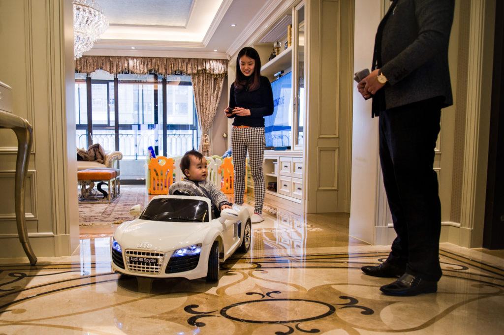 Shanghai (Cina), l'imprenditore Steven Zhu gioca con la moglie e il figlio piccolo, Radisson, in casa. 2014. © Alessandro Gandolfi
