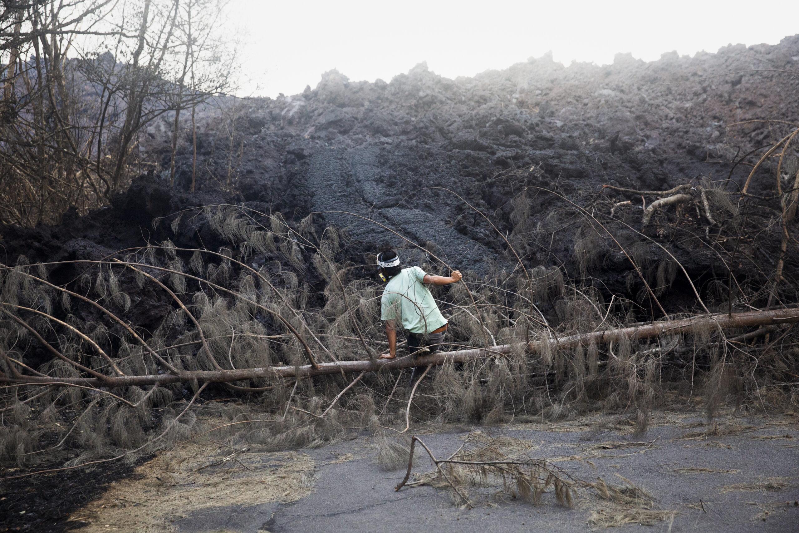 Roy Ruiz, 39 anni, residente nell'area di Seaview a Big Island, si arrampica nella foresta in lenta combustione mentre la lava dell'eruzione del vulcano Kilauea avanza nell'area di Opihikao di Big Island, Hawaii, Stati Uniti. 27 maggio 2018 © Gaia Squarci