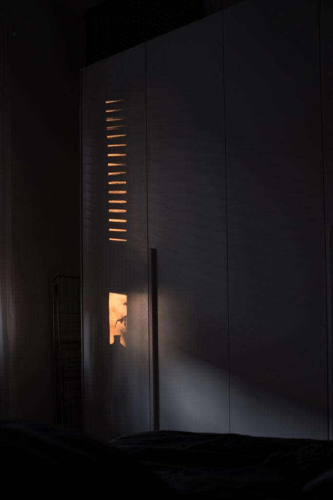 Spiraglio di luce entra da una finestra e fa intravedere le forme